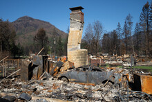 Home And Car In Detroit Oregon Totally Destroyed By The Beachie Creek Wildfire.  Chimney And Fireplace All That Remain.  Burned Trees On Mountain In Background