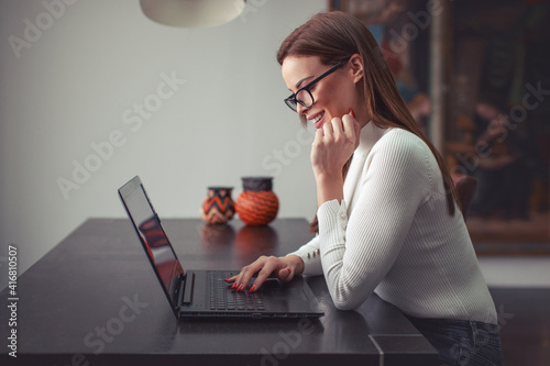 Happy young smart woman communicating by laptop Tapéta, Fotótapéta