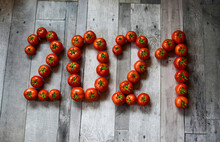 Figures Of The Year Laid Out With Freshly Picked Tomatoes