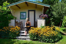 A Woman Sitting On The Stairs Of A Garden Shed, Reading A Book.