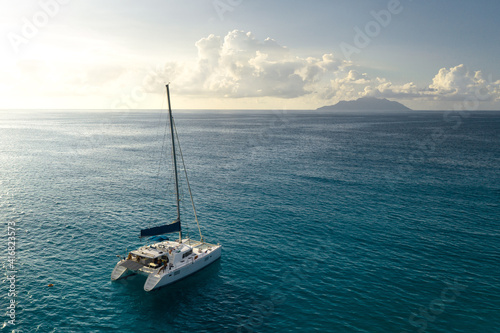 Leinwand Poster Eco yacht catamaran sailing in ocean at sunset. Aerial view