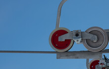 Red And Silver Wheels Of  Ski Chair Lift Pulley On Cable With Blue Sky Background Silver Metal Large Cable And Round Red Wheel Geometric Shapes Empty Space For Type Horizontal Format