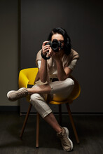 A Beautiful Girl In Light Clothes Sits On A Chair With Her Legs On Her Knee And Holds A Camera In Front Of Her Face