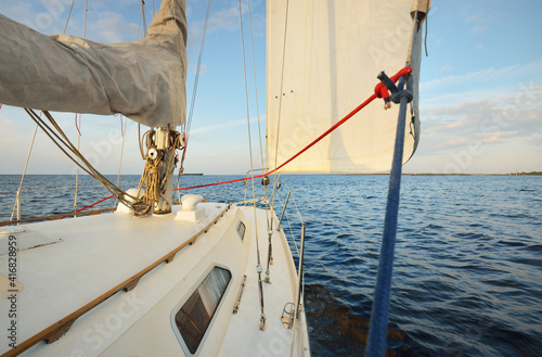 Fototapeta White sloop rigged yacht sailing in the sea at sunset. Clear sky. A view from the deck to the bow, mast, sails. Transportation, travel, cruise, sport, recreation, leisure activity, racing, regatta obraz na płótnie