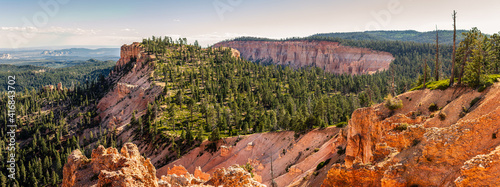 Billede på lærred Panorama shot of pink sandstone mountains with green conifers on top in Bryce ca