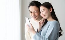 携帯を見る日本人カップル