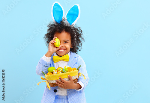 Fotografiet Funny little black child covering eye with Easter egg and smiling