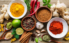 A Selection Of Various Colorful Spices On A Wooden Table In Bowls And Spoons