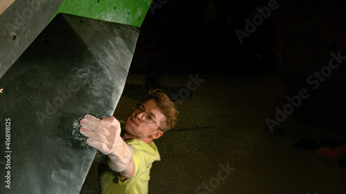 Fototapeta CLOSE UP: Strong man bouldering indoors firmly grips the edge of a volume hold