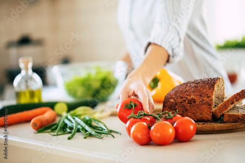 Fotografia, Obraz Close up photo of young smiling woman is preparing a fresh healthy vegan salad w