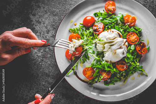 Fototapeta woman eating healthy salad with burrata cheese, arugula salad and tomatoes obraz