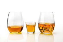 Whiskey Or Whisky Three Glasses, One Served Neat, One Short And One With Ice Cubes Isolated On White Background