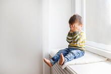 Portrait Of Adorable Little Boy Sitting On The Windowsill And Crying. Upset Child Covering His Face At Home. Barefoot Kid Hiding Behind Palms Of His Hands. Close Up, Copy Space, Background.