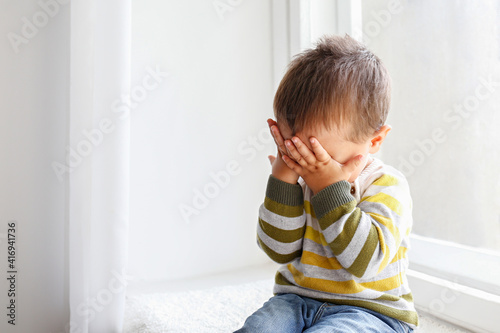 Portrait of adorable little boy sitting on the windowsill and crying Fototapet