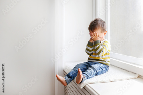 Cuadros en Lienzo Portrait of adorable little boy sitting on the windowsill and crying