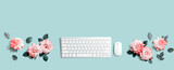 Computer keyboard and a mouse with pink roses - flat lay
