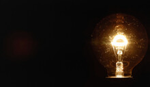 A Vintage Ball-shaped Light Bulb On A Black Background. Room For Copy-space On The Left.