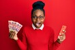 canvas print picture - Young african american woman using smartphone holding south africa rand banknotes celebrating crazy and amazed for success with open eyes screaming excited.