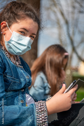 Two young girls seated on a bench in the city park using tablets wearing masks in pandemic time © jovannig