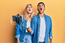 Young Interracial Couple Taking A Selfie Photo With Smartphone Angry And Mad Screaming Frustrated And Furious, Shouting With Anger Looking Up.
