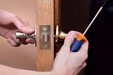 Door Installation, Worker Installs Door Knob, Woodworker Hands Close Up. A Man Spins The Door Handle With A Screwdriver, Repairs The Door Handle Mechanism