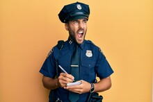 Handsome Hispanic Man Wearing Police Uniform Writing Traffic Fine Angry And Mad Screaming Frustrated And Furious, Shouting With Anger. Rage And Aggressive Concept.
