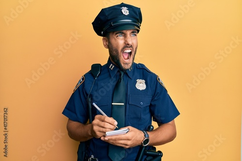 Fotografie, Obraz Handsome hispanic man wearing police uniform writing traffic fine angry and mad screaming frustrated and furious, shouting with anger