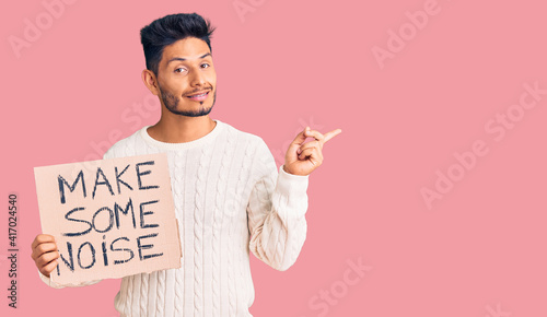 Fotografiet Handsome latin american young man holding make some noise banner smiling happy p