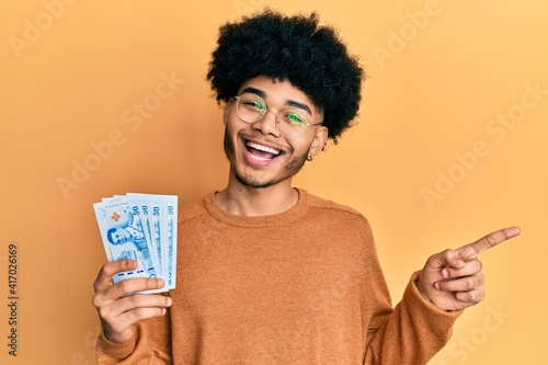 Fotografija Young african american man with afro hair holding 50 thai baht banknotes smiling