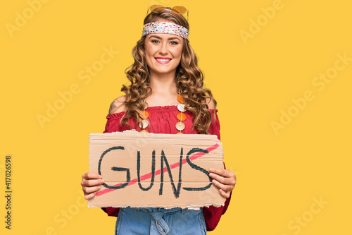 Young blonde girl wearing hippie style holding no guns warning banner looking po фототапет
