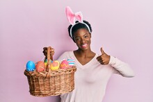 Young African American Girl Wearing Cute Easter Bunny Ears Holding Basket With Painted Eggs Smiling Happy And Positive, Thumb Up Doing Excellent And Approval Sign