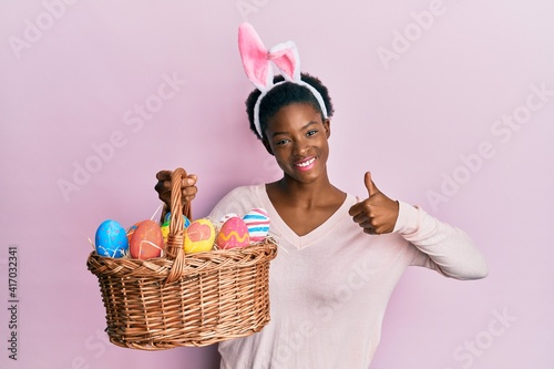 Canvastavla Young african american girl wearing cute easter bunny ears holding basket with p
