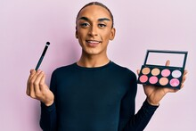 Hispanic Man Wearing Make Up And Long Hair Holding Makeup Brush And Blush Smiling With A Happy And Cool Smile On Face. Showing Teeth.