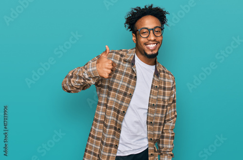 Young african american man with beard wearing casual clothes and glasses doing happy thumbs up gesture with hand. approving expression looking at the camera showing success.