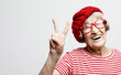 Old woman laugh and showing peace or victory signat camera. Emotion and feelings. Portrait of expressive grandmother.