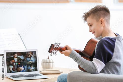 Fotografia Little boy taking music lessons online at home