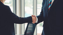Business People Handshake In Corporate Office Showing Professional Agreement On A Financial Deal Contract.