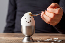 A Small Child Is Eating Soft Boiled Humpty Dumpty Egg Placed In Egg Cup On A Wooden Breakfast Table. She Uses Spoon To Eat The Egg From Its Shell. She Has Drawn A Smiling Face On The Shell.