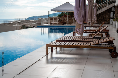 Fényképezés Luxury infinity pool and wooden deck chairs at the resort with beautiful sea views
