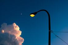 Illuminated Street Light And Pole Against Blue Evening Sky