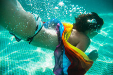 Horizontal View Of Unrecognizable Woman Diving Into Water Holding A Colorful Lgbt Flag. Lesbian, Gay, Bisexual And Transgender Iconic Colors. Gay Pride And Summer Holidays Concept.