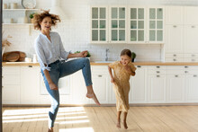 Hilarious Home Party. Emotional Family Young Single Mother And Small Daughter Having Fun Dance Listen To Music At New Modern Kitchen. Overjoyed Nanny Little Kid Girl Jump Barefoot On Warm Wooden Floor