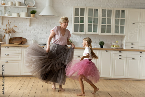 Fototapeta Merry leisure time. Happy energetic grandmother teach ball dance active little child. Caring grandma junior girl grandkid engaged in dancing in funny large fluffy skirts barefoot on warm kitchen floor obraz