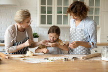 Little Cook. Happy Mature Elderly Grandma Adult Mom Explain Small Daughter Grandkid How To Cut Funny Cookies From Rolled Dough Praise For Success. Dynasty Of 3 Diverse Females Baking Biscuits At Home