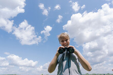 Young White Kid Looking At Camera Holding Black Vintage Binoculars In Hands Isolated On Sunny Summer Bright Blue Sky Background. Portrait Of Cute Happy Smiling And Laughing Boy