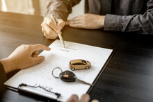 A Car Rental Company Employee Pointed Out The Renter To Sign The Rental Agreement After Discussing The Details And Rental Terms With The Renter. Concept Of Car Rental.