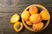 Fresh Apricots In A Wooden Plate. Fruits Are Scattered On A Wooden Table.