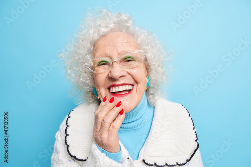 Obraz People old age positive emotions concept. Happy grey haired lady smiles broady has white even teeth wears bright makeup dressed in casual sweater happy to spend time with family isolated on blue - fototapety do salonu