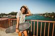 Leinwandbild Motiv Beautiful and fashion young woman posing with a skateboard.