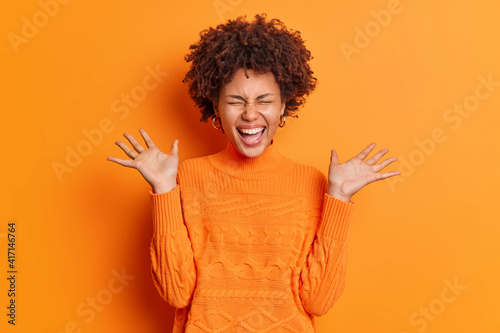 Fotografía Positive overjoyed young African American woman raises palms feels very glad expresses joy dressed in casual jumper isolated over orange background